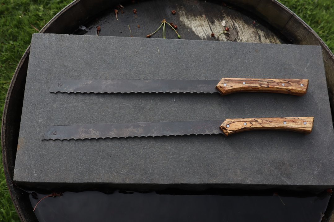 Två brödknivar av omsmitt riktigt gammalt bandsågsblad, skaftade med rötad bok från en av smedjans städkubbar. Slits på @byvägen35  Set of two bread knifes, reforged from old bandsaws blade, halted with splatted beech. Now in service at @byvagen35 #återbruk #österlen