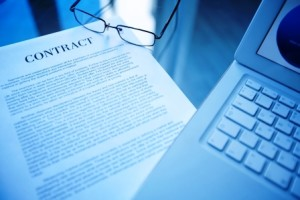 Image of document, eyeglasses and laptop on workplace