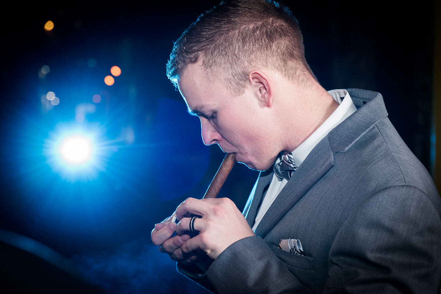 Portrait of a groom lighting up a cigar with a blue light in a background.