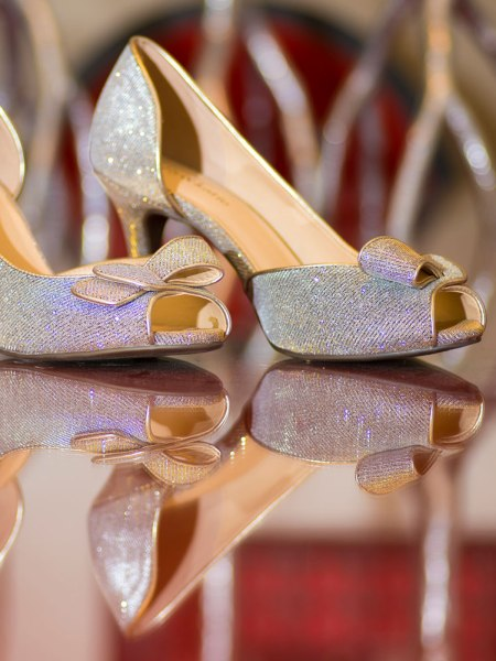 Brides shoes on a red table at Blackstone Hotel reflection off of the surface