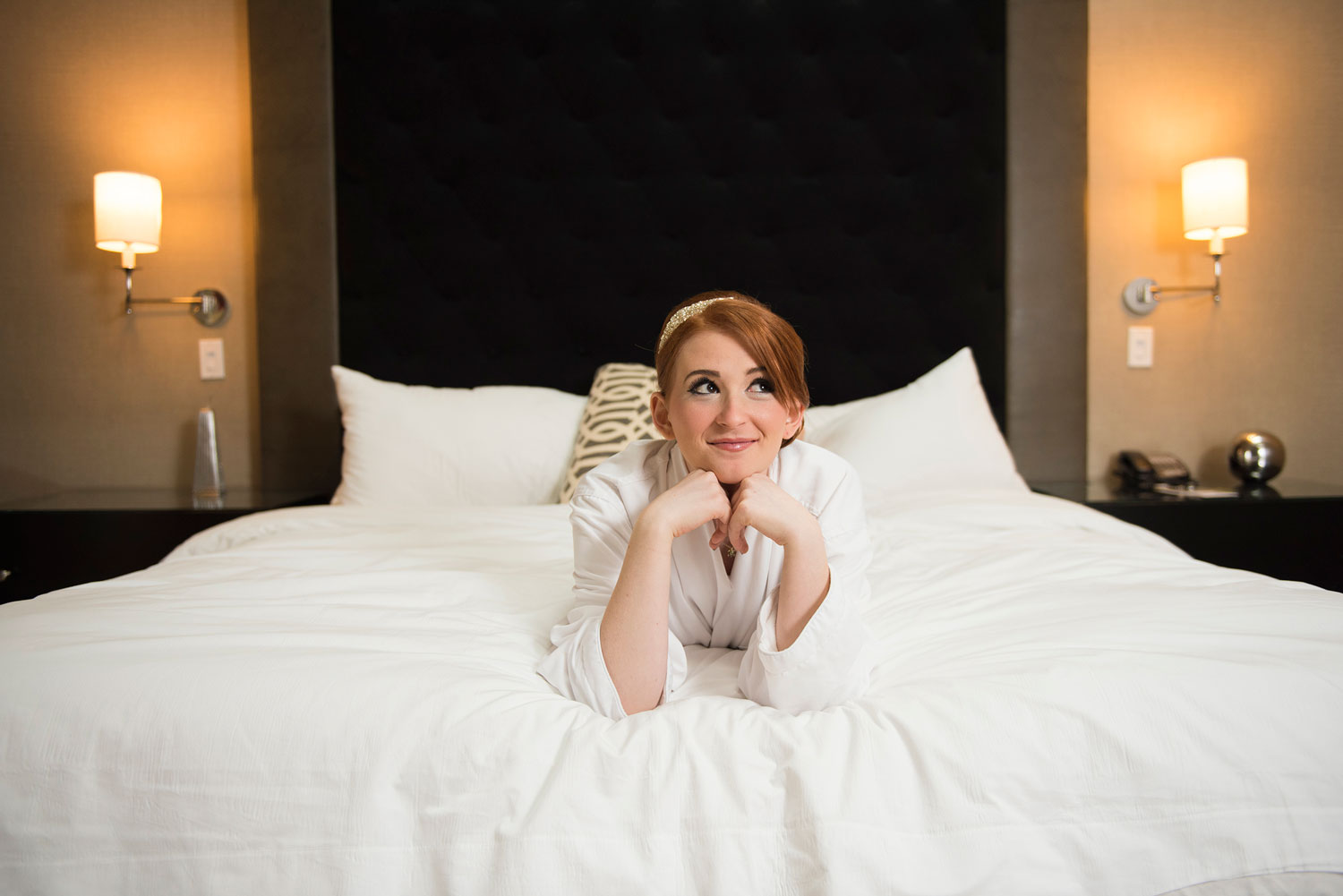 Bride laying down on her bad smiling before her wedding at blackstone hotel.