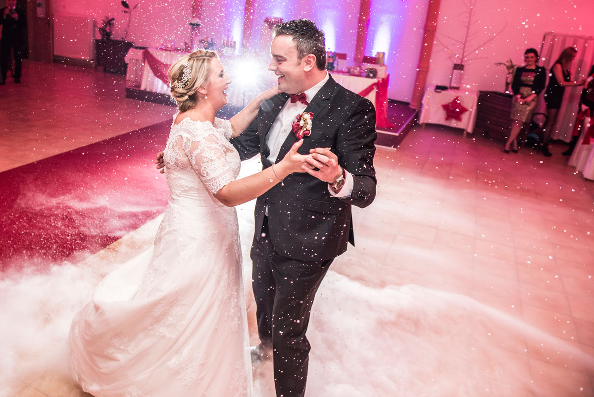 Bride and groom dancing while snowing, back light with a star light.