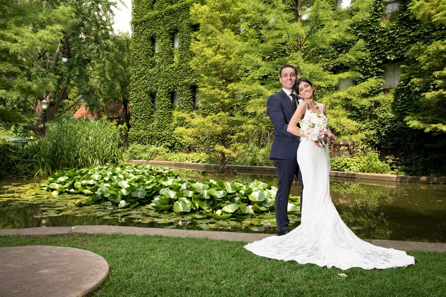 Wedding portrait of bride and groom in the green garden surrounded by water