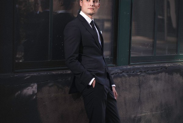 Groom leaning on an industrial window looking over his shoulder