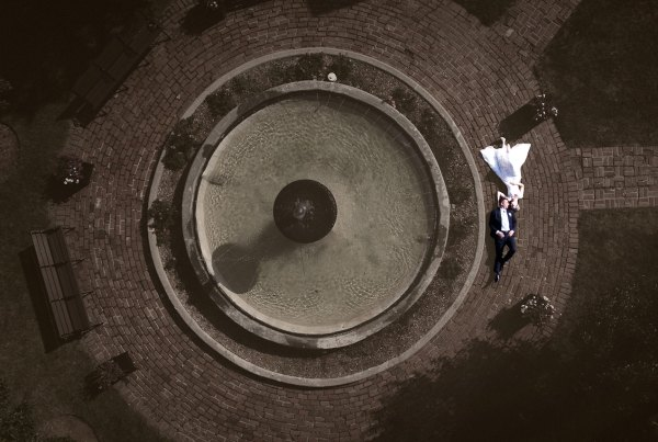 aerial portrait of bride and groom laying next to fountain
