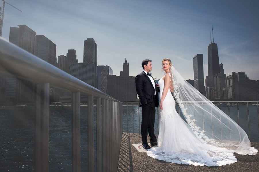 Chicago Wedding photograph of bride and groom before Chicago Skyline with brides veil flying into air.