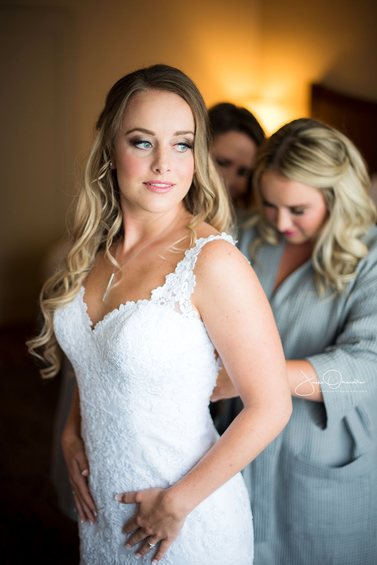 bride getting ready in her dress being helped by bridesmaids