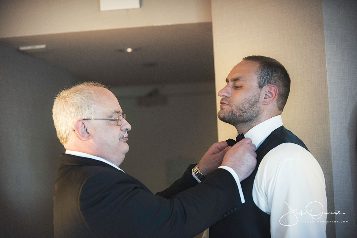 father helping groom put his tie on