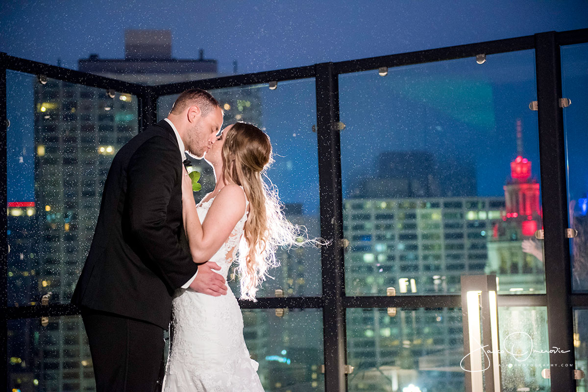 bride and groom kissing in the rain on the rooftop