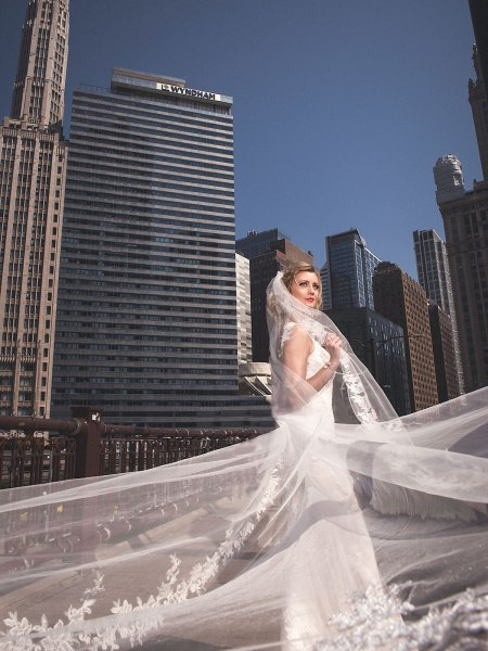 Bride holding her beautiful cathedral veil with Chicago city in the back