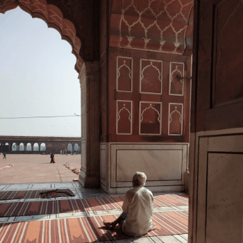In the Image is a man praying at the Jama Masjid in Delhi India