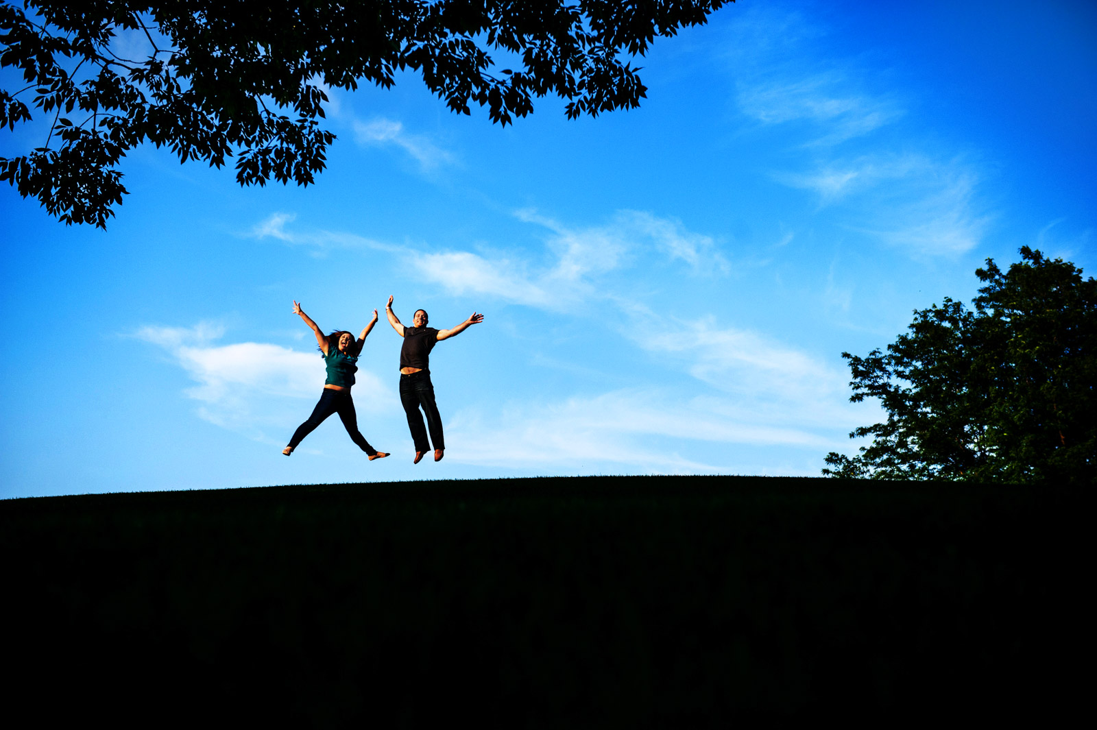 Couple jumping for joy on a hill at sunset during their engagement session