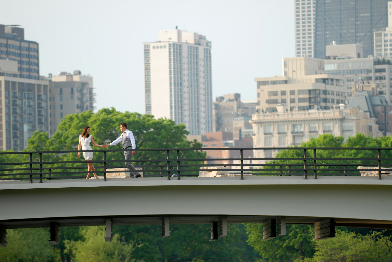 Engaged couple holding hands on bridge in Lincoln Park Zoo South Pond