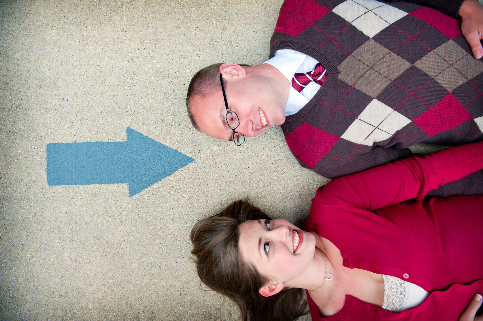 Engagement Session couple laying on the ground with arrow pointing to them