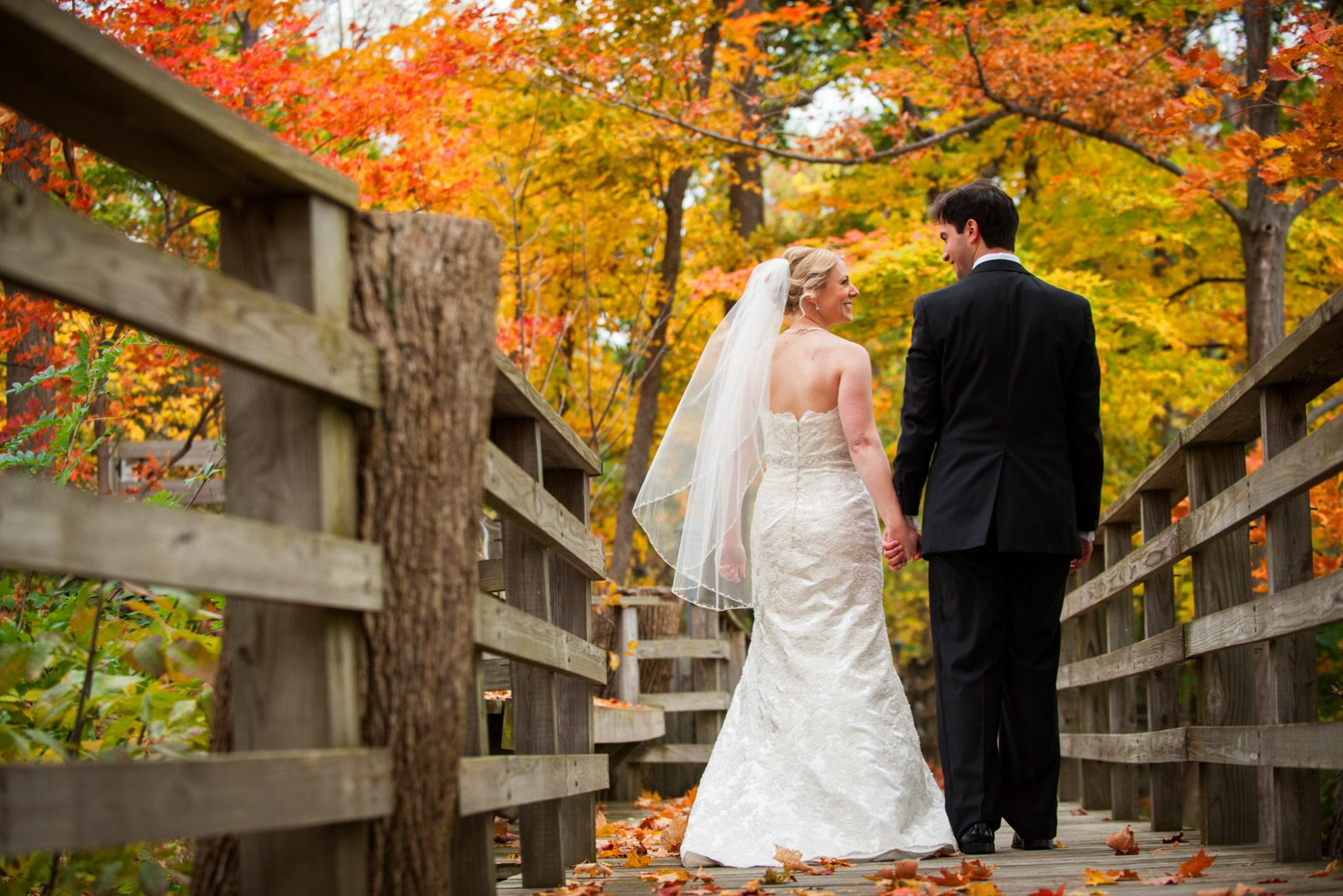 Bride and Groom walking down path hand in hand during their Fall outdoor wedding ceremony