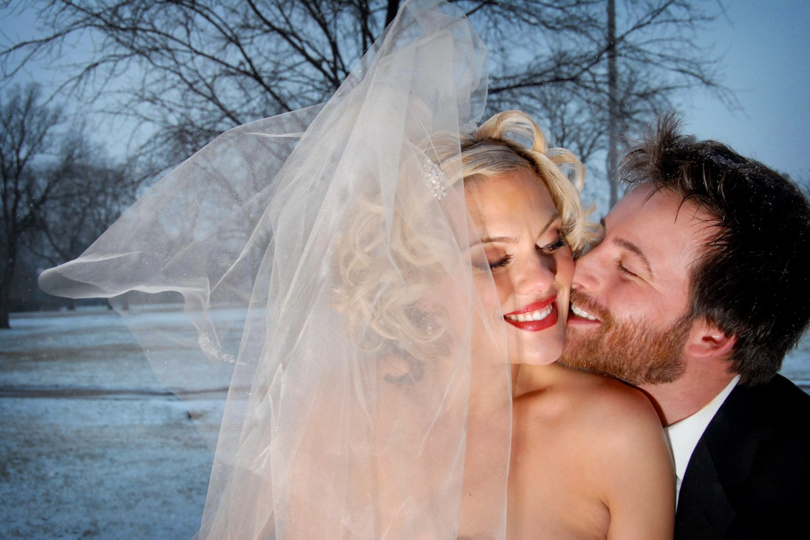 Bride's veil blowing in the winter with snow on the ground and groom cuddling with bride