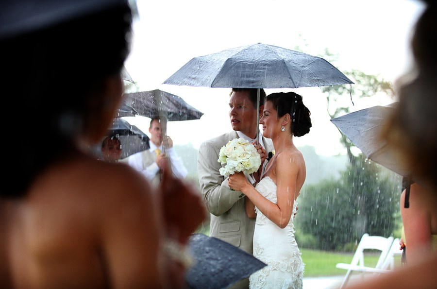 Bride and Groom under umbrella in rain at ceremony