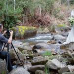 photographer Jason Robins taking an image of bride and groom on the Delatite River near Pinnacle Valley resort in Merrijig