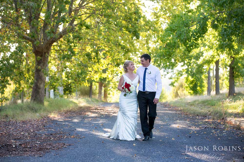 Bride and Groom walking down tree lined path at Lake Hume