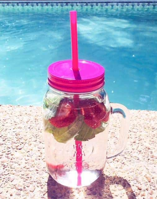 infused water in cup with strawberries and basil