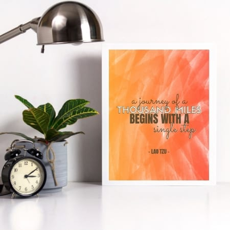 decluttering quote in frame next to plant, clock, and lamp