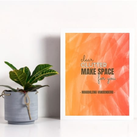 decluttering quote in frame next to plant