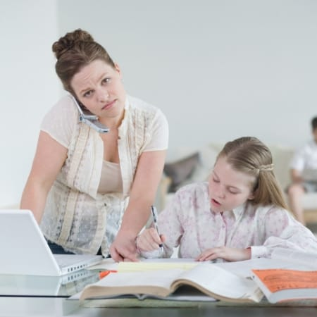 Learn how to declutter your mind by single tasking. Woman multi tasking with daughter.