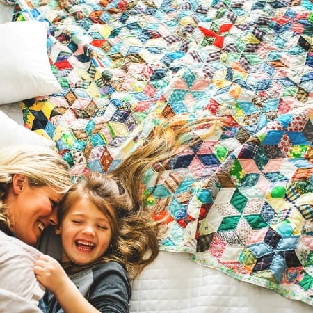 decluttering sentimental items with mom and daughter on bed with treasured quilt