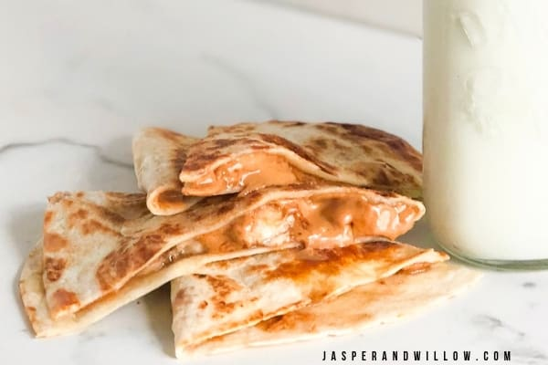 peanut butter and banana quesadilla snack with glass of milk
