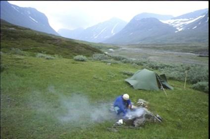 Álggavágge i bakgrunden. Grönt ryggåstälti i vinden. I förgrunden gör jag upp en eld som ryker.