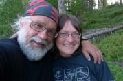 En gammal gråskäggig man med glasögon och buff håller om en ung mörk kvinna med glasögon. De ler bägge två och verkar vara förälskade