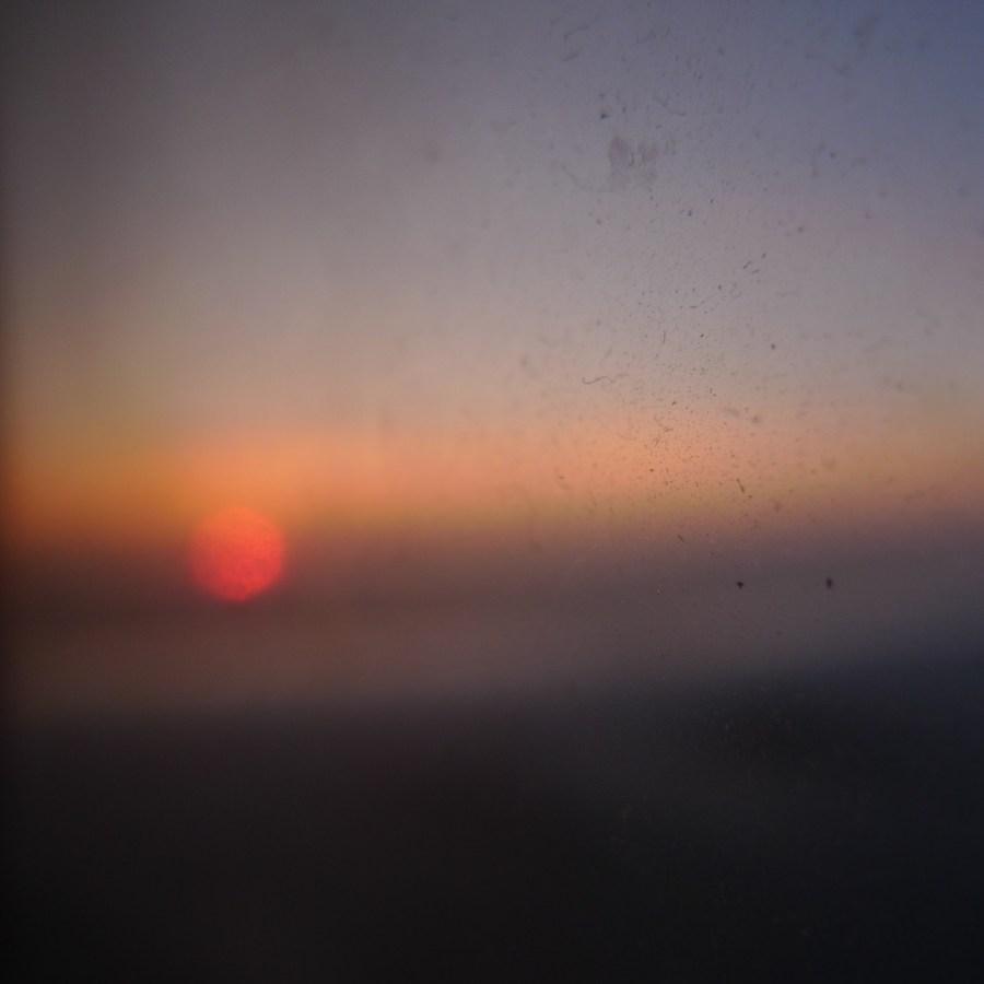 En oskarp bild av en solnedgång från en flygplansfönster