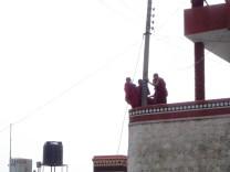 Munkar som hänger vid en elstolpe på klostermuren