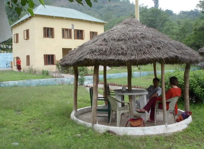I bakgrunden ett stort gult hus, vid huset står en man i röda kläder, mannen är tibetan. Under ett solskydd av halm sitter två personer vid ett bord.