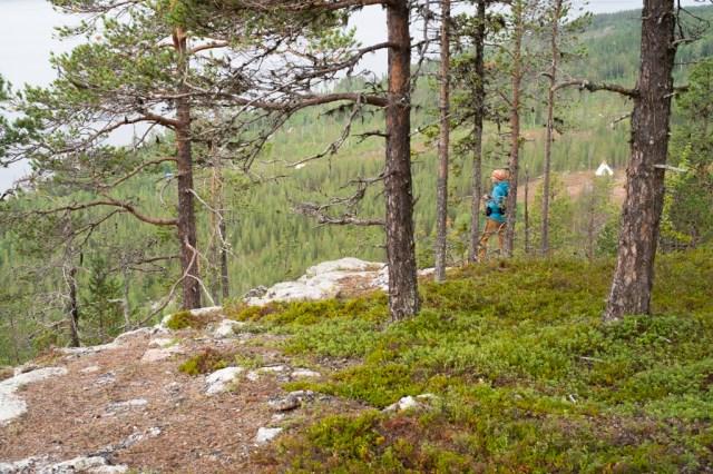 En människa står på berget, vid branten och bakom honom syns en teepe på ett kalhygge.