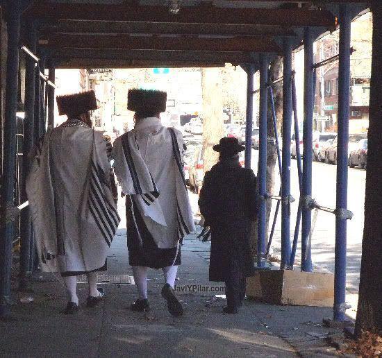 El shtraimel que lucen estos dos hombres parece más festivo. Atención al aspecto del chico. Visitando el barrio judío jasídico de Brooklyn (Nueva York) en Sabbath.
