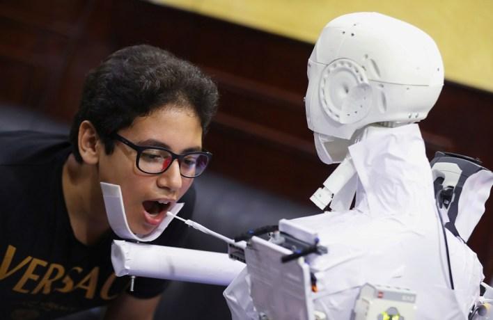 """يقوم """"Cira-03""""، بإجراء فحوص الكورونا بتثبيت ذقن الشخص ومد ذراع آلية لأخذ مسحة من الفم."""