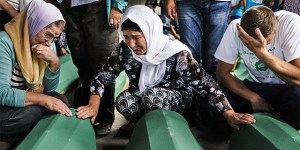 People mourn over coffins of their relatives in Srebrenica on July 9, 2015 where 136 bodies found in mass grave sites in eastern Bosnia will be reburied on 20th anniversary of the Srebrenica massacre. Nearly 8,000 men and boys from the enclave were captured and systematically killed by Bosnian Serb forces in the days after the fall of Srebrenica on July 11, 1995. AFP PHOTO / DIMITAR DILKOFF (Photo credit should read DIMITAR DILKOFF/AFP/Getty Images)