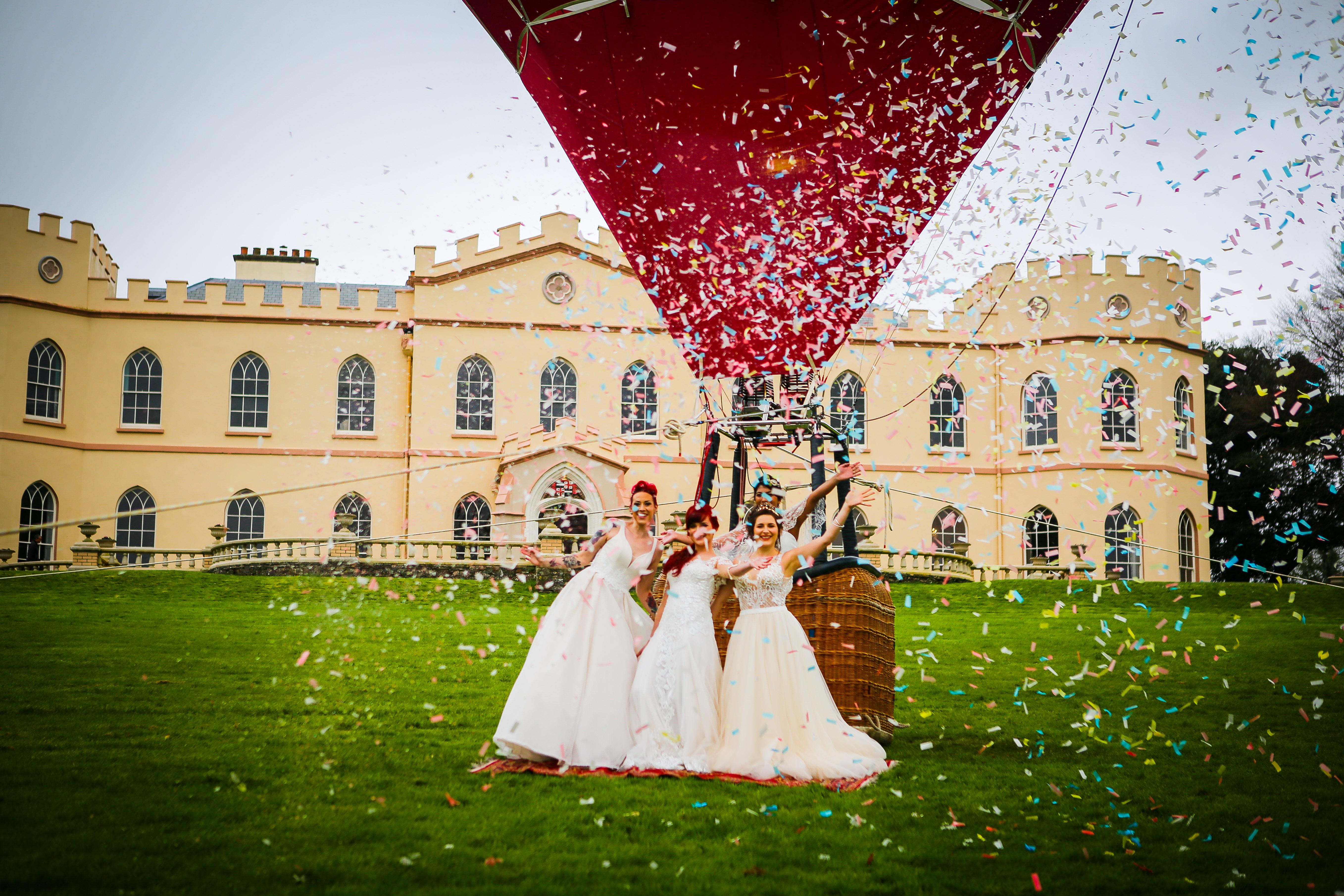 3 brides in fron of tawstock with confetti canon