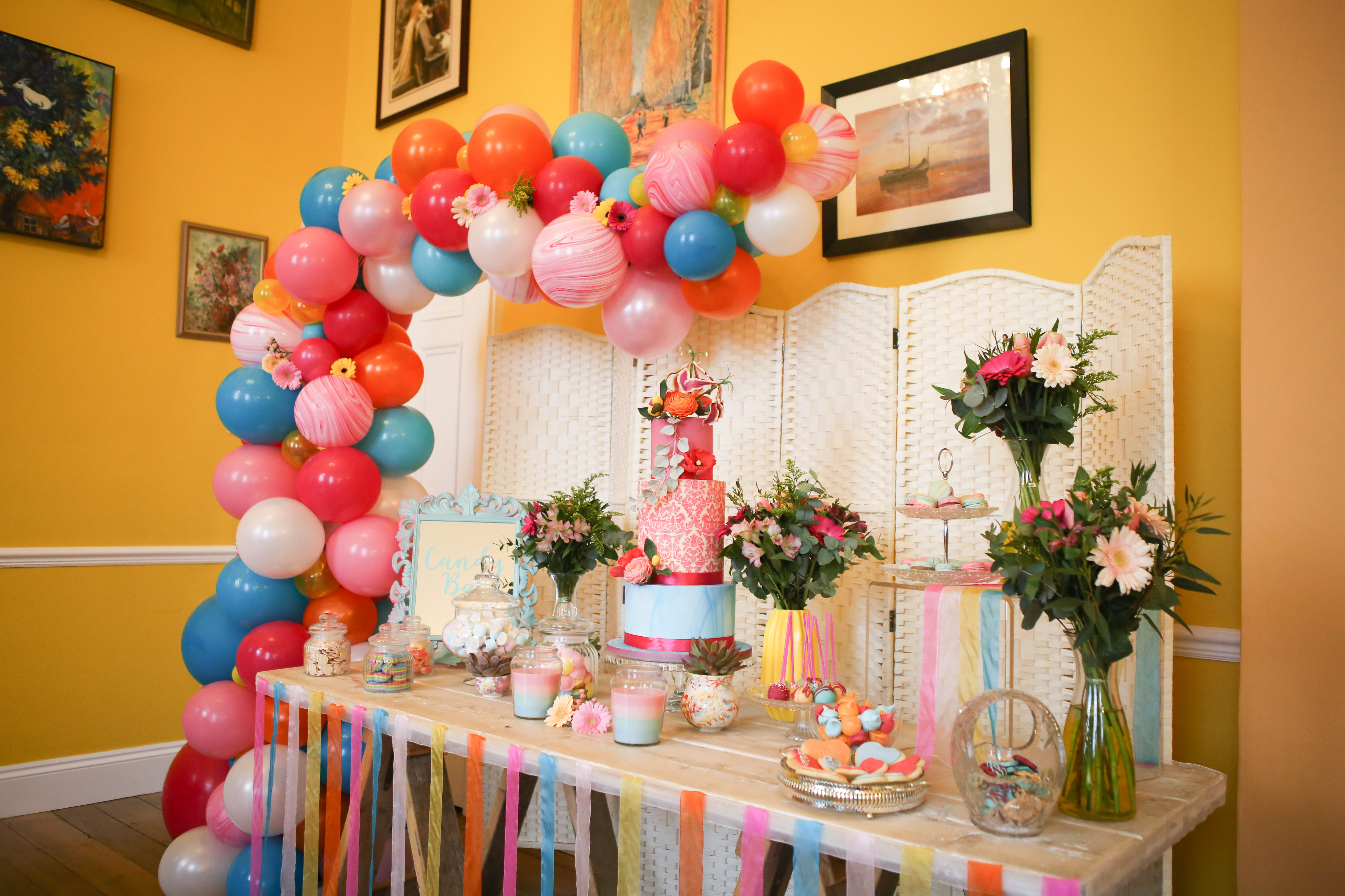 Cake table with colourful balloon arch