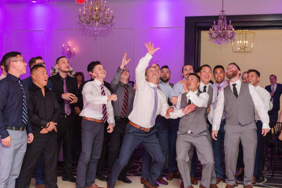 the boys catch the garter, the men go for the garter, men having fun catching the garter