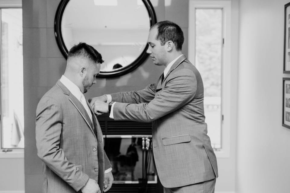 assisting the groom get ready black and white, donning the boutonniere black and white photo