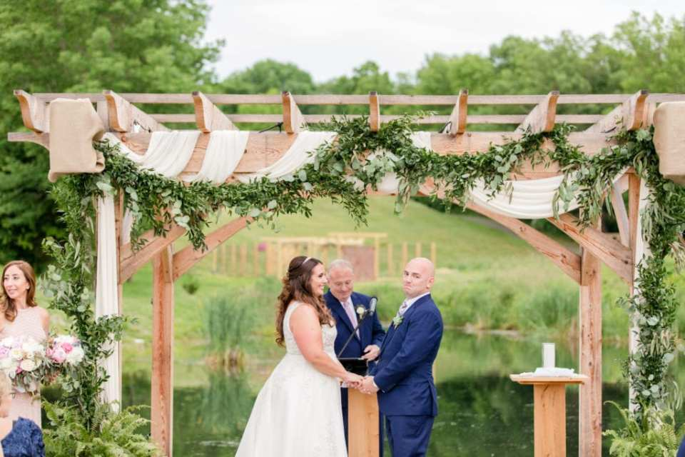 bride and groom at ceremony altar with arbor and eucalyptus hanging from it