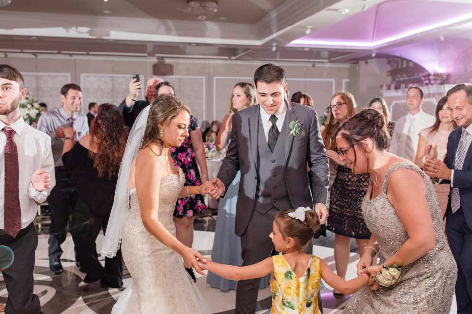 heartwarming reception shot, bride and groom dance with child guest, fun reception photo