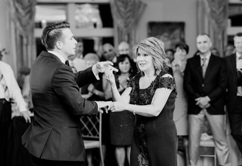 groom dances with mother black and white photo
