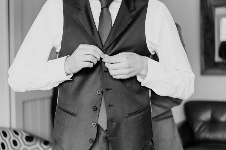 vest up, male putting on vest for vow, black and white photo