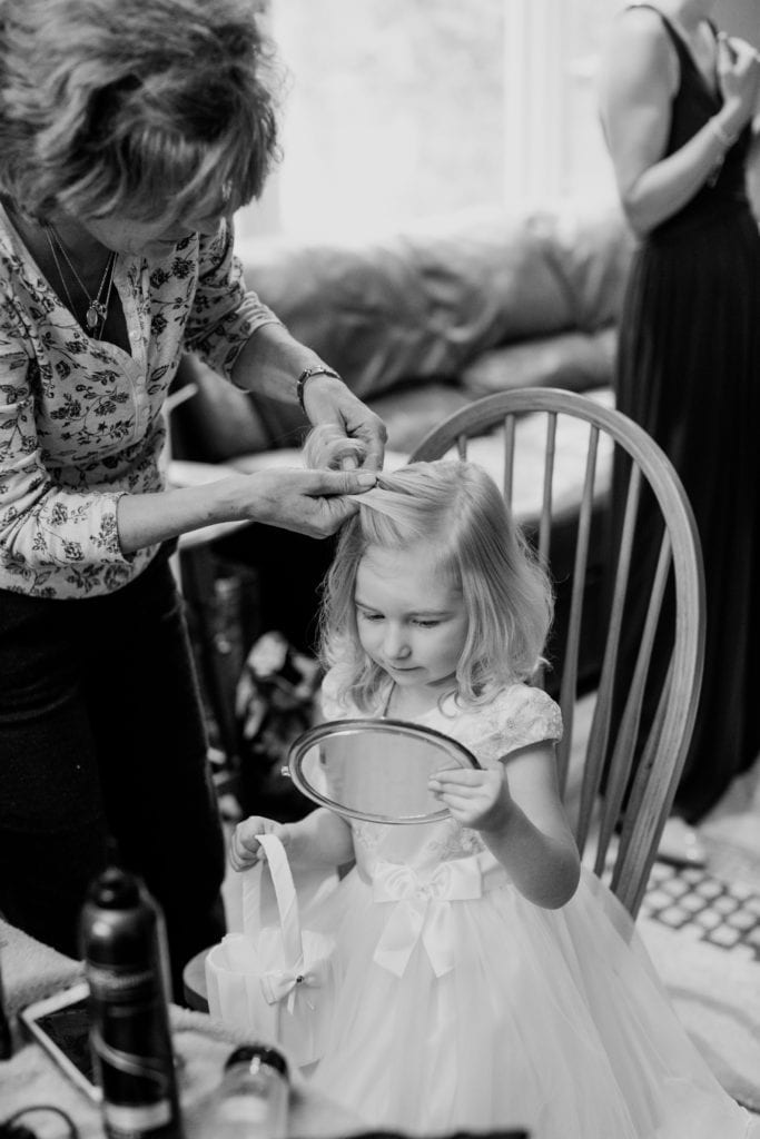 black and white photo of flower girl looking at herself in a mirror while getting her hair done