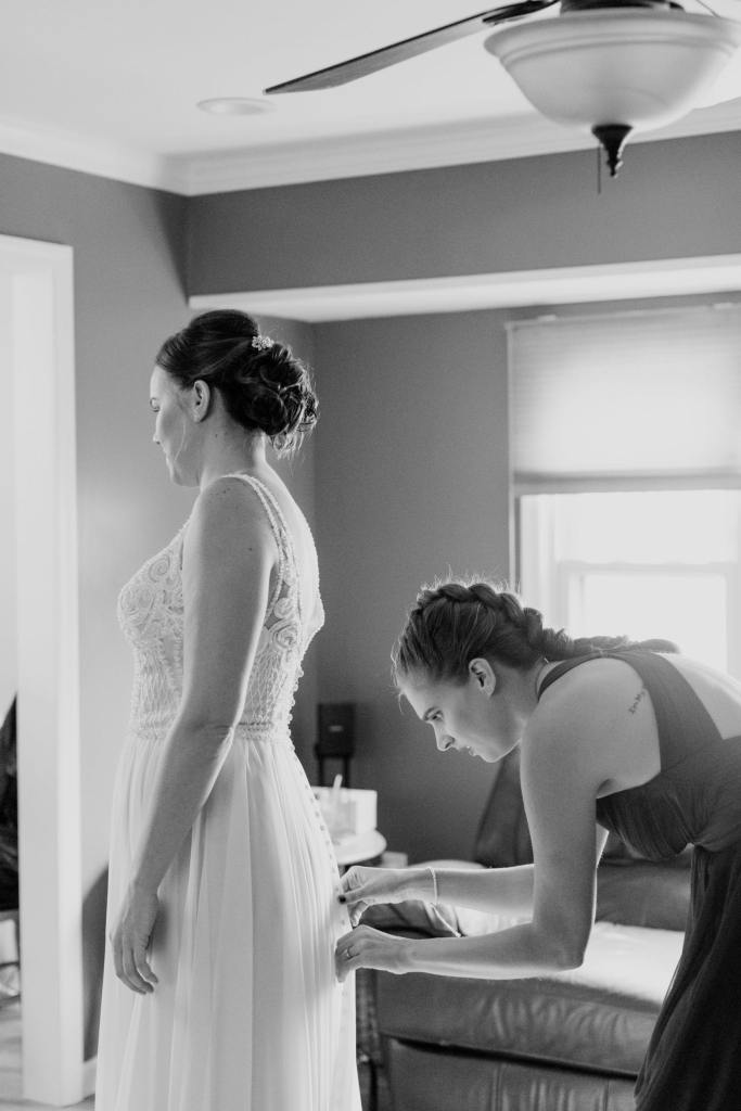 black and white photo of bride being buttoned into her gown by a member of the bridal party