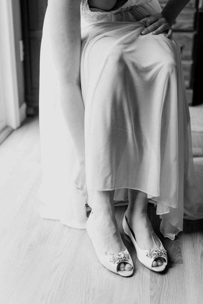 black and white photo of bride putting on her white flat open toed shoes with rhinestones at the toe