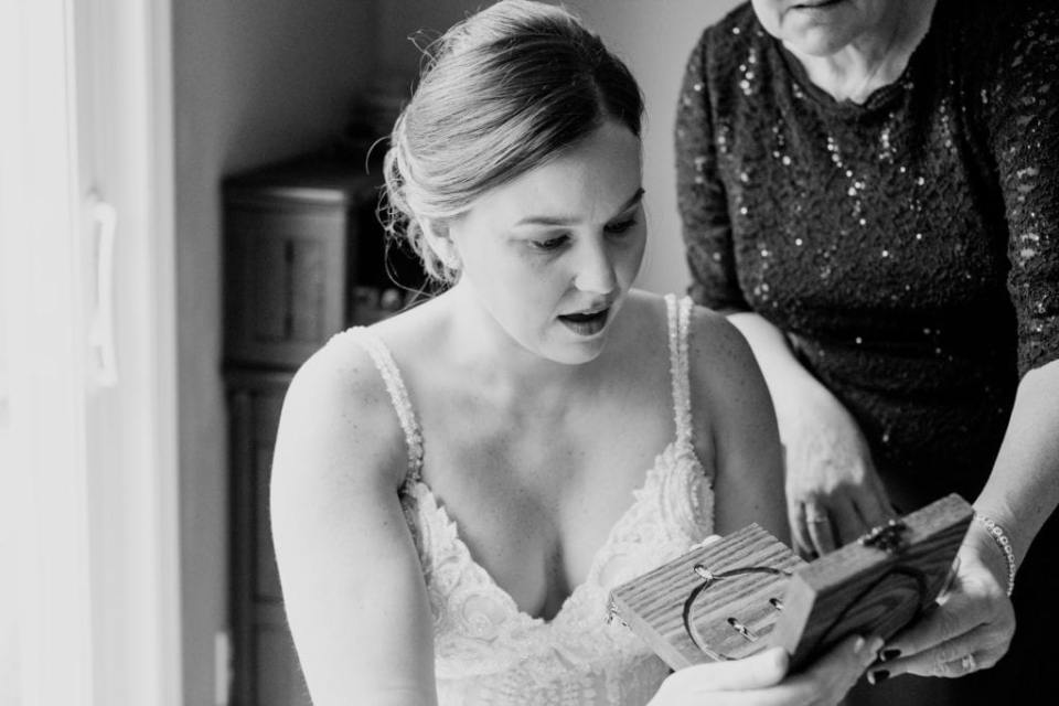 black and white photo of bride showing surprise while opening a wooden box with a heart carved into it
